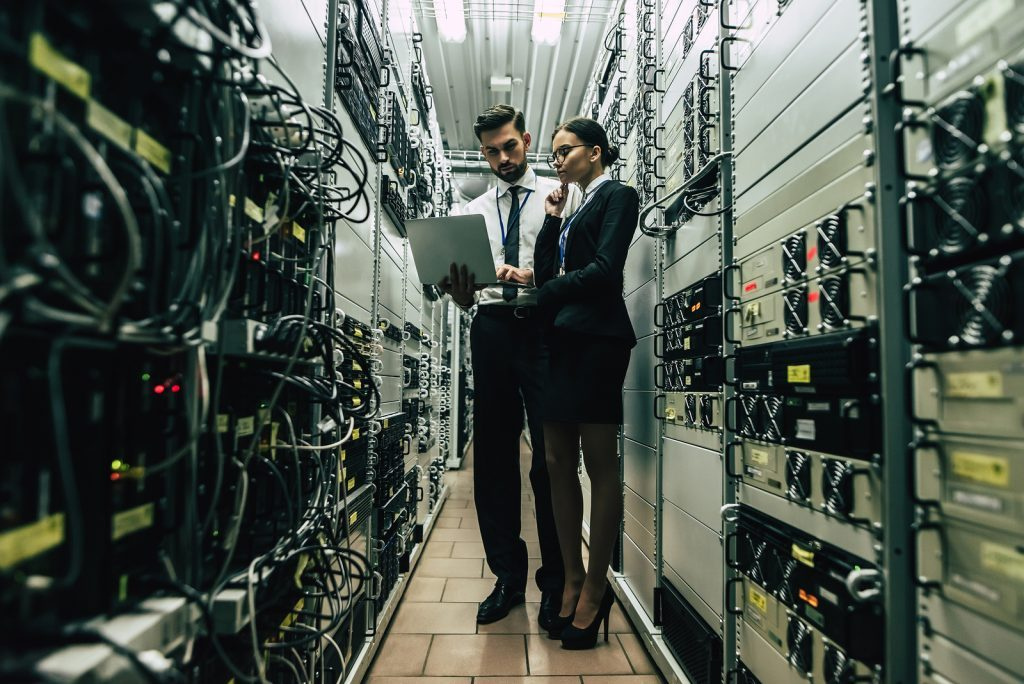 IT professionals in a server room conducting an infrastructure risk assessment.