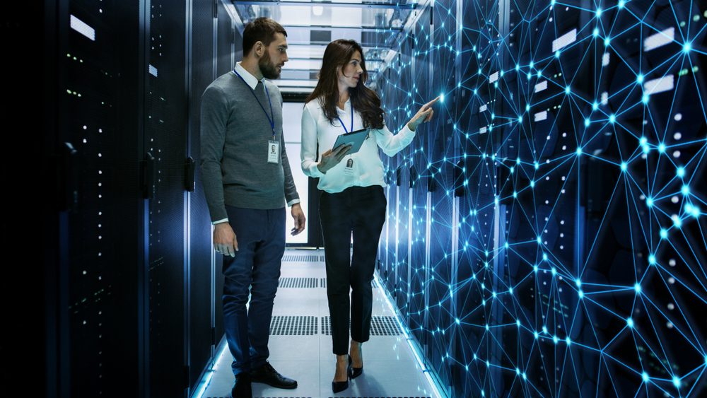 Two IT professionals in a data center discussing future improvements for IoT technology.